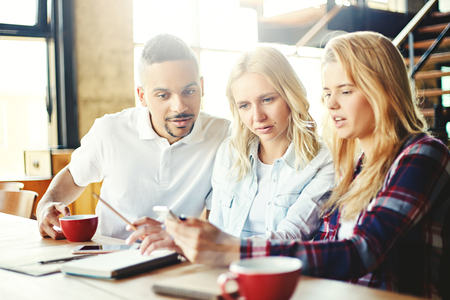 Group of three curious college students sitting at desk and looking at smartphone screen together, using app or browsing pictures Stock Photo