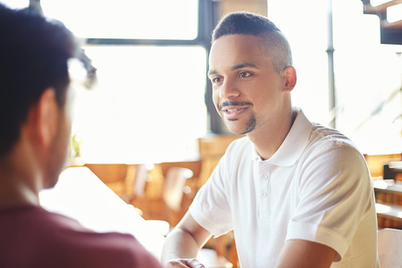 Mixed race young man talking to his unrecognizable friend while sitting at table in cafe