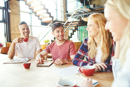 Grupo de jóvenes compañeros de trabajo alegres que se divierten en la pausa para el café - charlando con el café y riendo