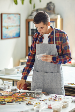 Casual man in gray apron laying out colorful mosaic on table creating beautiful piece of art Reklamní fotografie
