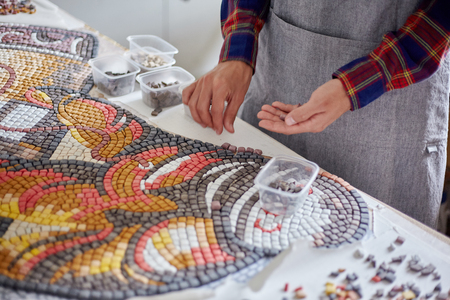 Faceless shot of man arranging mosaic pieces in colorful ornamental image Stockfoto