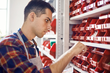 Side view of young man standing at shelves with red containers and choosing mosaic pieces Фото со стока - 122025652