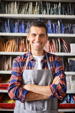 Happy young man smiling at camera wearing apron and standing in colorful workshop of mosaic master