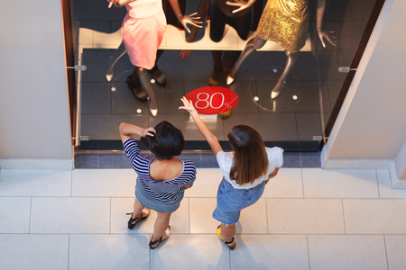 High angle view of two girls standing before window display in fashion store and discussing luxury stylish dresses on mannequins being on sale with eighty percent off discount