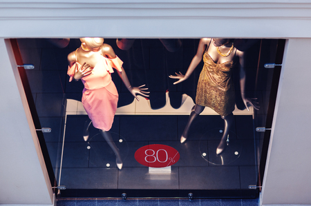 From above shot of window shop with mannequin in trendy clothes and label saying sale
