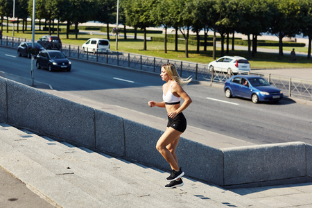 Side view of young lady in sportswear running up street steps during outdoor training on sunny day