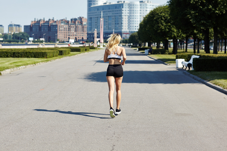 Back view of female athlete running away from camera on asphalt path during outdoor workout on sunny day 스톡 콘텐츠