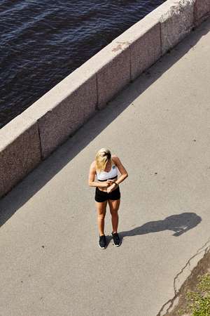 From above shot of unrecognizable female in sportswear standing on asphalt path near river and looking at fitness tracker during outdoor workout on sunny day Stockfoto