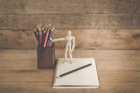 correspond: Robot standing holding a pencil on notebook,retro vintage style