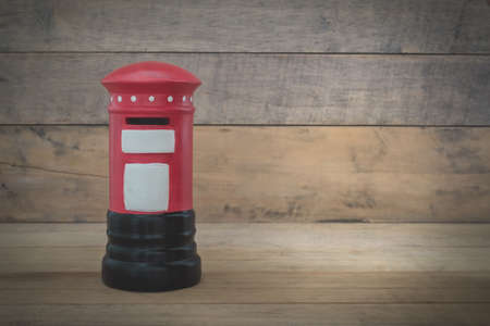 red post box: Small red post box on wood background