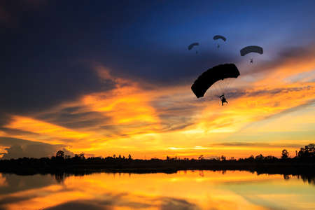eventide: parachute at sunset silhouetted