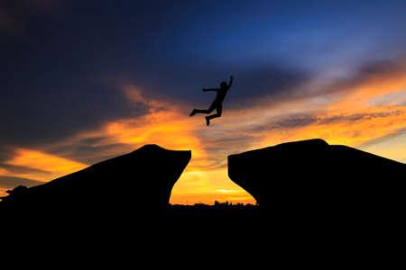 difficult lives: Man jump through the gap between hill.man jumping over cliff on sunset background,Business concept ideasundown; sunrise; sunset; thailand; water; winter