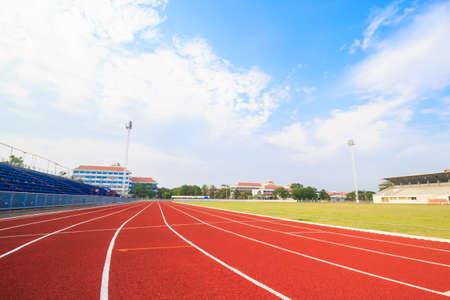 carrera de relevos: Pista de atletismo, césped verde y azul cielo.