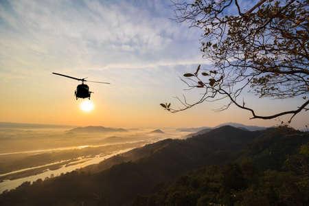 Silhouet van helikopter met zonsondergang.
