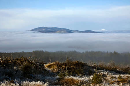 Picturesque image of Knockmealdown Mountains protruding from the fog covering Araglin Valley in County Waterford,Ireland.