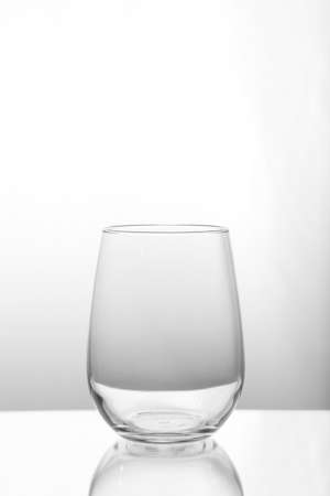 An empty glass cup against a white background