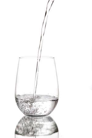 vaso con agua: El agua que se vierte en un vaso de vidrio sobre un fondo blanco