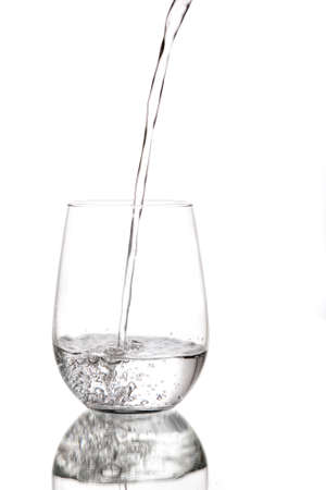 Water being poured into a glass cup against a white background