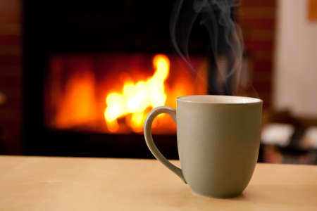 comfortable: A coffee cup filled with a steaming liquid in front of a fireplace