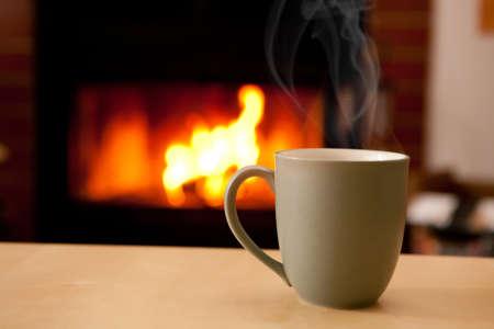 chocolate caliente: Una taza de caf� llena de un l�quido humeante delante de una chimenea Foto de archivo