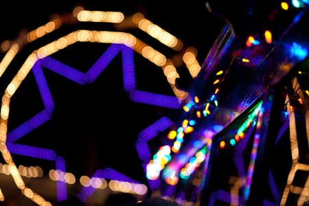 Abstract lights arranged as decorations on a variety of buildings and carnival rides