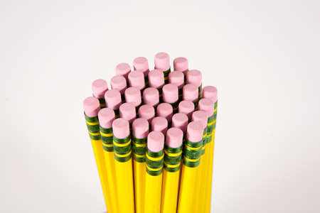 Several pencils and erasers on a white background