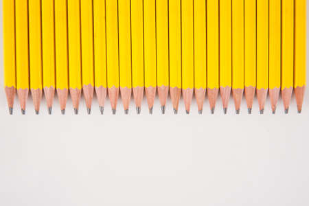 A group of sharpened, yellow, #2 pencils laid out in a row on white. Фото со стока