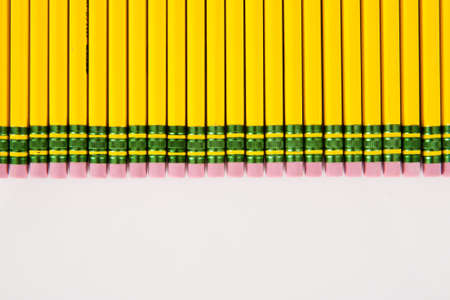 A group of yellow, #2 pencil erasers laid out in a row on white. Фото со стока
