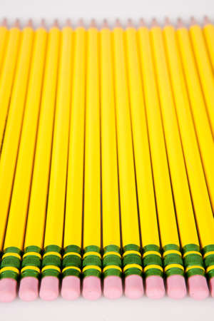 A group of yellow, #2 pencil erasers laid out in a row on white. photo