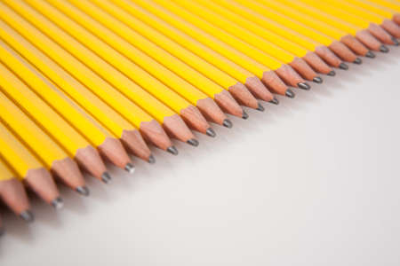 A group of sharpened, yellow, #2 pencils laid out in a row on white. photo