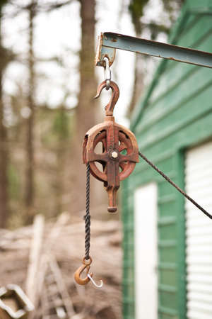 A rusty metal pulley with a rope and hook.