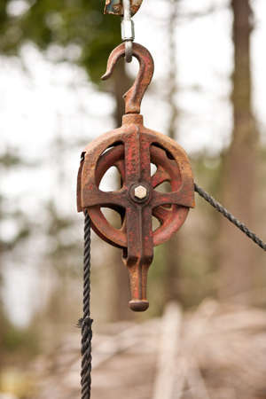A rusty metal pulley with a rope.