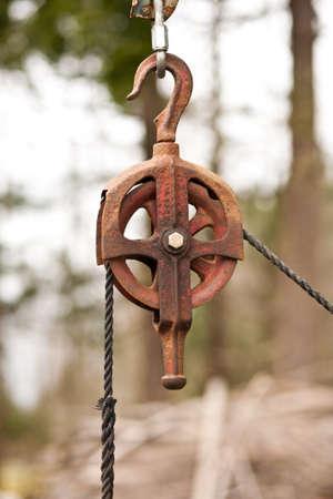 polea: Una polea de metal oxidado con una cuerda. Foto de archivo