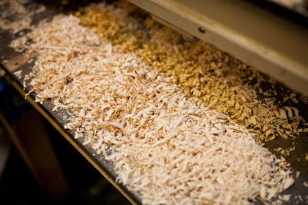 A pile of wood shavings and saw dust on a workshop bench.