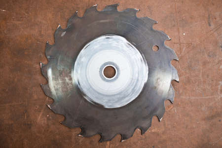 A circular saw blade on a brown table.