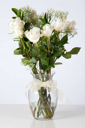 White roses in a clear, glass vase set against a white background  Фото со стока