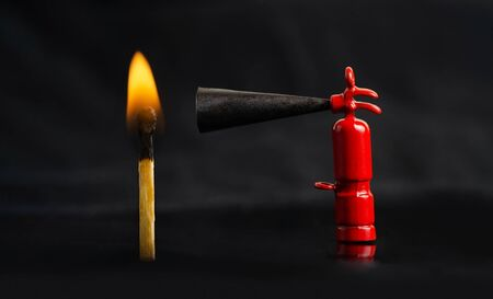 Tiny fire extinguisher close to a burning match against a lit black background, macro shot Stockfoto