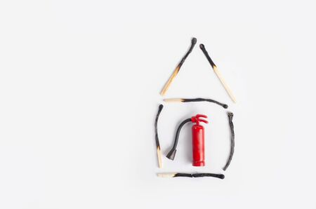 Fire insurance concept. Small house made of burnt matches with a miniature fire extinguisher inside