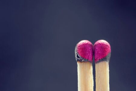 Two slightly burnt matches standing next to each other and forming a heart-shaped pattern against a violet background Stock Photo