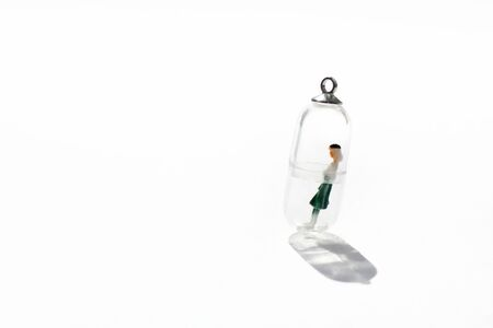 A miniature figure of a woman isolated inside a small glass capsule. Social distancing conception for stay home campaign during quarantine Imagens