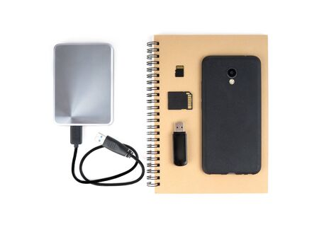 A set of storage devices - paper notebook, portable hard drive, SD card and mobile phone isolated on white. Traditional and modern ways of data storage.