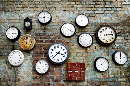 A lot of vintage clocks of different sizes hanging on a grunge brick wall. Round and square clocks show different time. Some of the clocks have no hands.