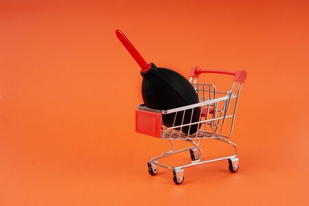 Mini shopping cart carrying a dust blower for camera and lens cleaning.
