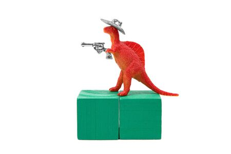 Toy tyrannosaurus rex wearing a cowboy hat and holding a revolver in his arm stands on two green wooden blocks. Close-up shot, isolated on white. Wild West dueling dinosaur concept. Stockfoto
