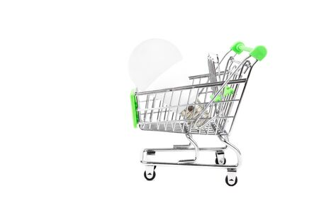 Environmentally friendly LED light bulb in a miniature shopping cart. Close-up shot, isolated on white. Power consumption and greenhouse emissions reduction concept.