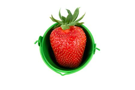 Fresh strawberry in a small green bucket. Top view, isolated on white. Organic fruit concept: a bucket with vitamin C, fiber, antioxidants, and more packed in a tiny heart-shaped berry. Stock fotó