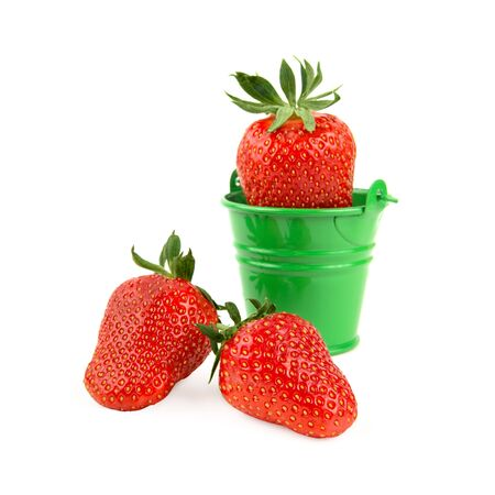 Fresh strawberry in a tiny green bucket and two ripe strawberries isolated on white background. Close-up studio shot. Organic fruit harvesting season.
