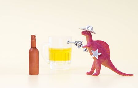Toy dinosaur wearing a cowboy hat, holding a revolver in his arm and having a sheriff star shoots an empty beer bottle on a neutral background. Fight against alcohol-related problems concept.