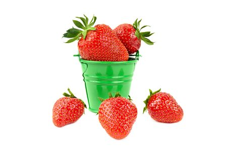 Juicy fresh strawberries in a small steel bucket and three loose berries isolated on white background. Close-up, selective focus. Gardening multivitamin organic fruit. Healthy taste of summer concept.