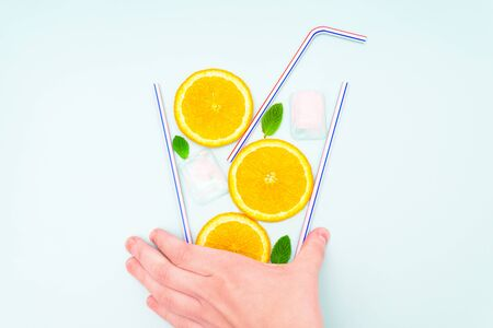 Creative flat lay arrangement of orange slices, fresh mint leaves, ice cubes and drinking straws in the shape of a glass with refreshing summer cocktail held by a female hand on light blue background.